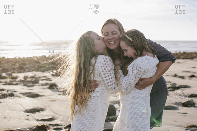 Two girls hug their mom on the beach