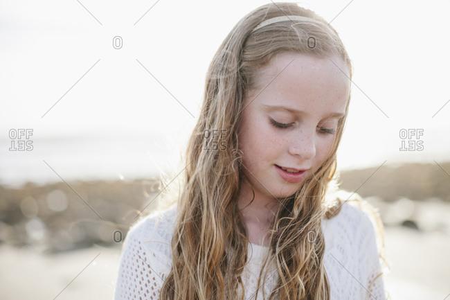 A little girl looks down on the beach