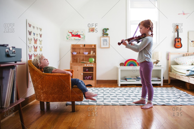 A girl plays the violin for her brother