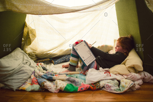 A girl writes in a blanket fort