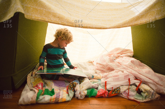 A boy reads a book in a blanket fort