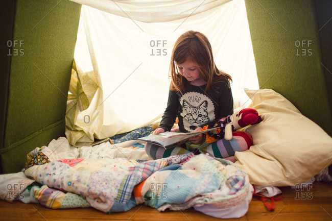 A girl reads in a blanket fort