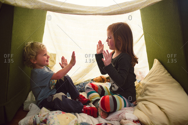 A girl and her brother play in a blanket fort
