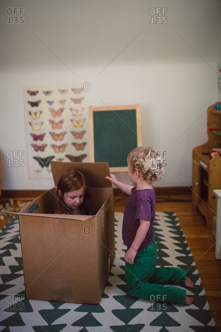 A brother and sister play in a box