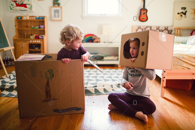 A brother and sister play with cardboard boxes