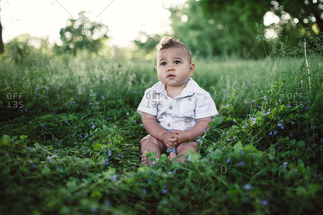 A baby sits in a field of grass
