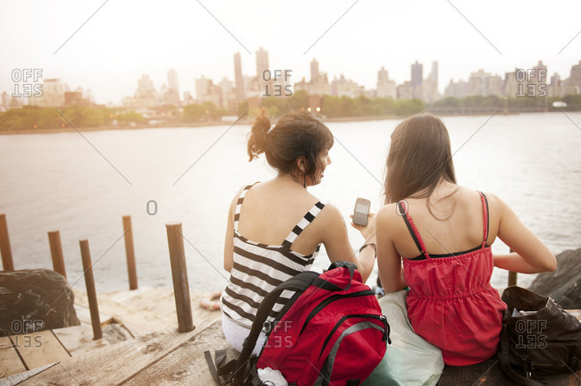 Two young women sharing texts by East River