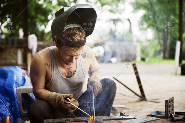 Man welding in tank top with tattoos