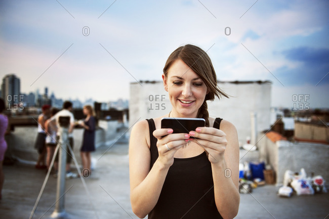 Young woman on phone on rooftop