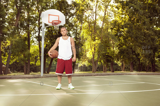 Young man standing with basketball on outdoor court
