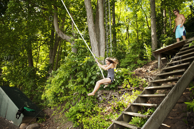 Young woman swinging on rope swing