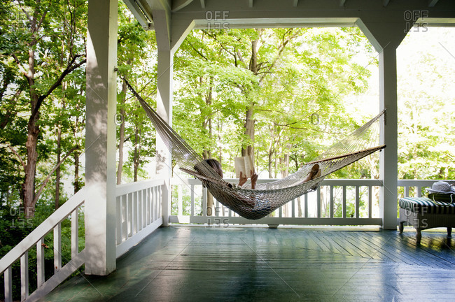 Woman relaxing with book on hammock