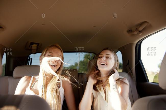 Female friends laughing in car