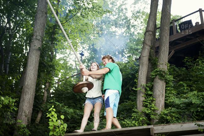Man helping woman onto rope swing