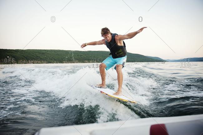 Young man wake surfing on lake