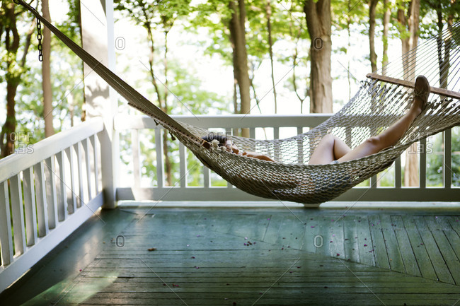 Young woman relaxing on porch hammock