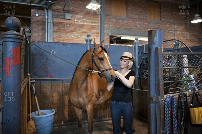 Woman with horse in barn