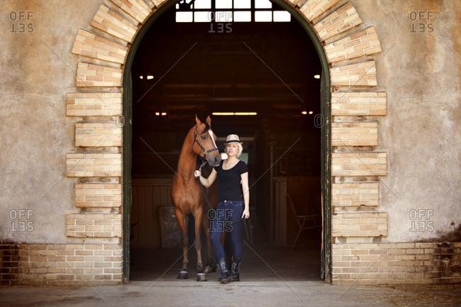 Woman with horse in barn doorway