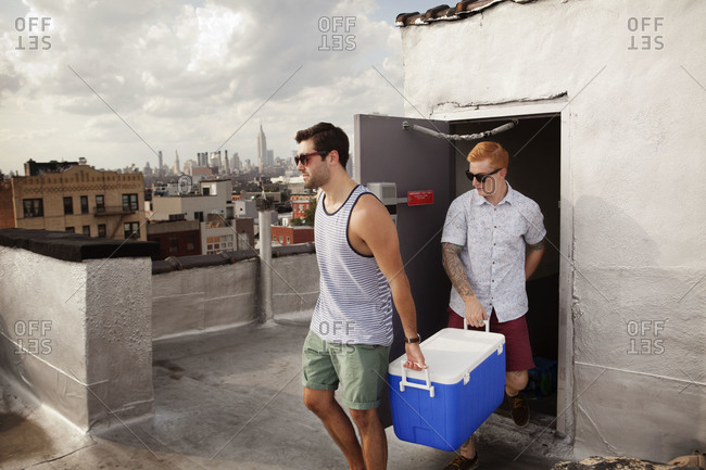 Two male friends carrying cooler to roof