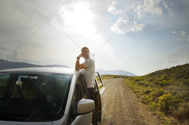 Young man standing out of van door on dirt road
