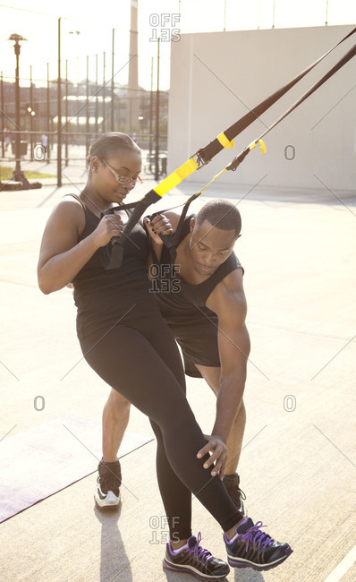 Trainer helping woman with exercise