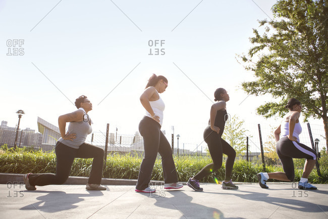 Women doing lunges in park