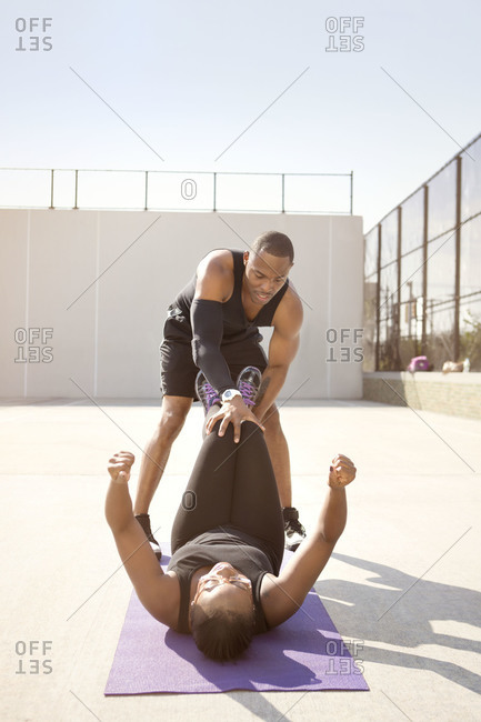Trainer helping woman with sit ups