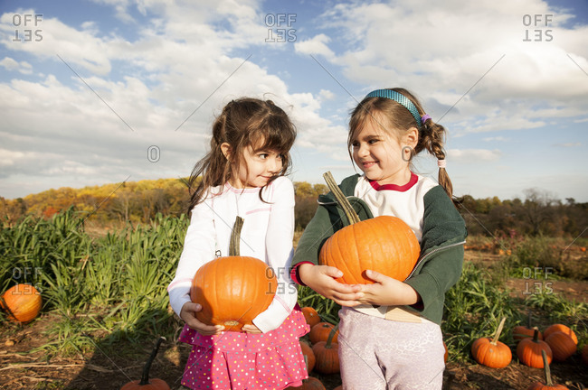 Two girls holding pumpkins in patch