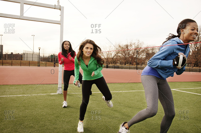 Three women exercising in football field