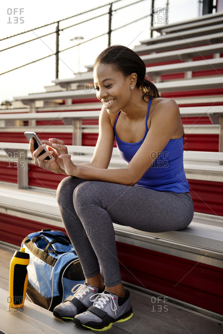 Woman texting on bleachers after a work out