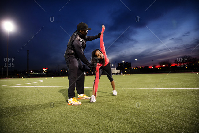Trainer assisting woman in stretch