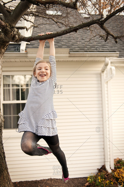 Young girl hanging from tree in yard