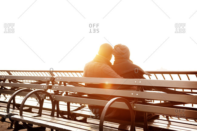 Young couple sitting on bench watching sunset