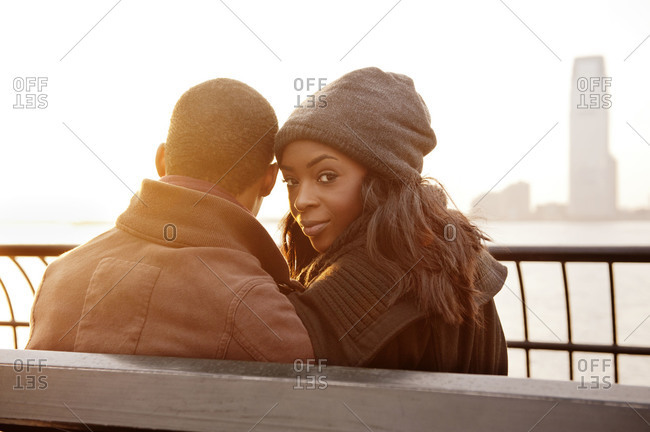 Young couple sitting on bench woman looking back