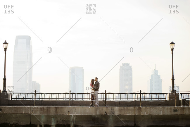 Young couple embracing each other on city bridge
