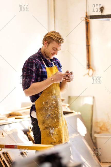 Carpenter in workshop using phone