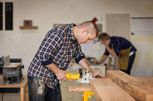 Carpenter in workshop putting clamp on board