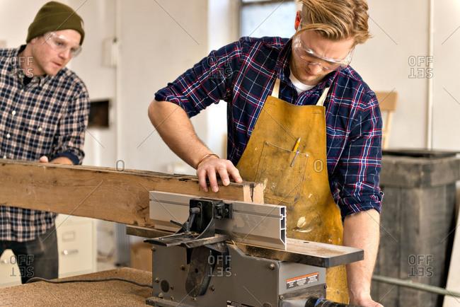 Two carpenters guiding plank through saw