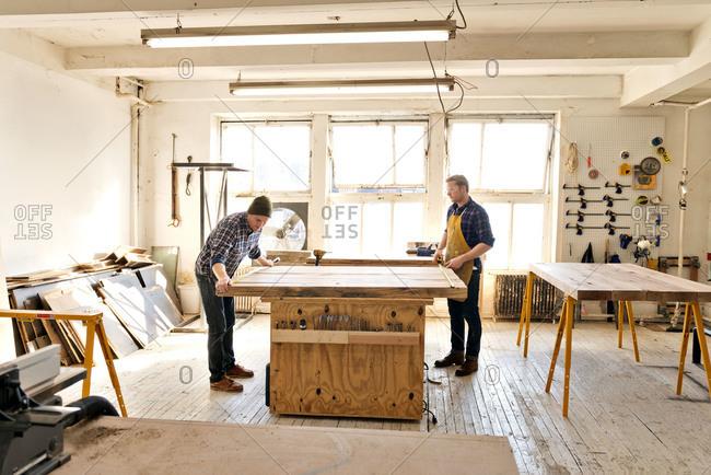 Two carpenters measuring wood in workshop