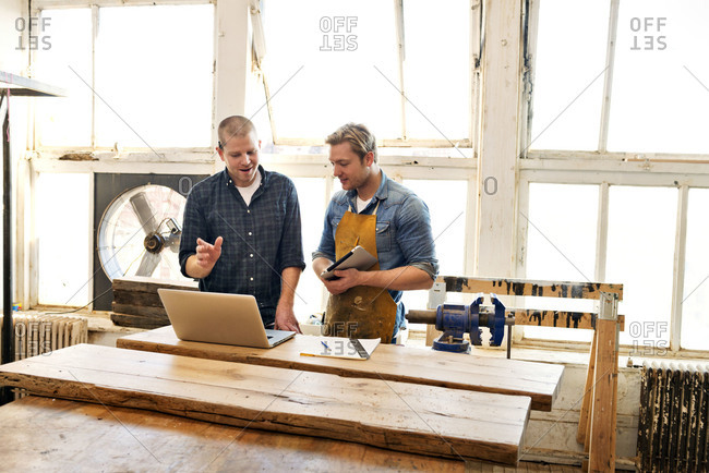 Two carpenters looking at laptop in workshop