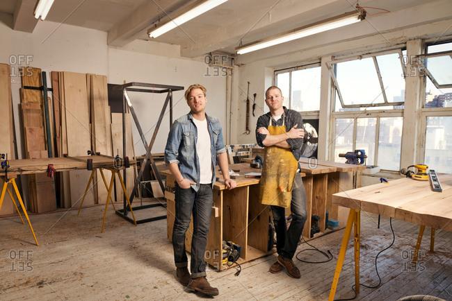 Two carpenters posing in workshop