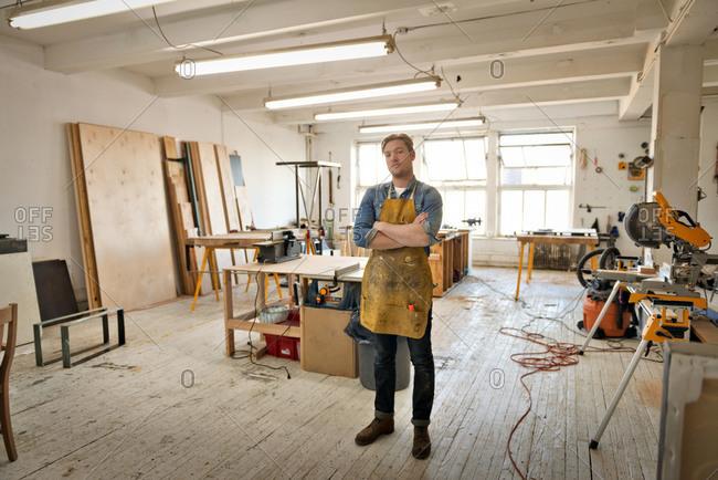 Proud carpenter posing in workshop