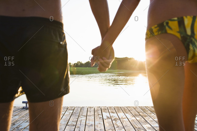 Close up of couple holding hands on jetty