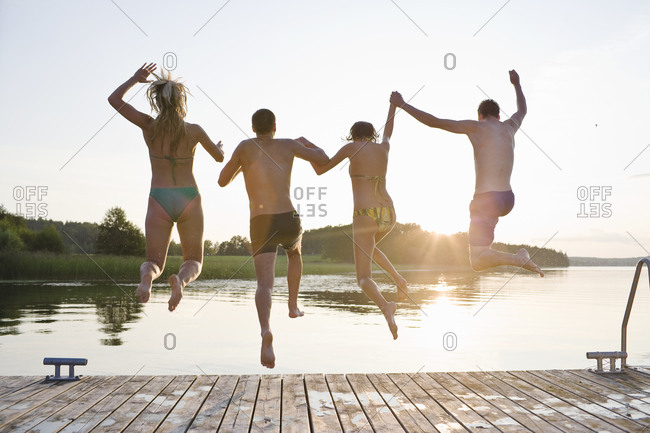 Four people jumping into lake