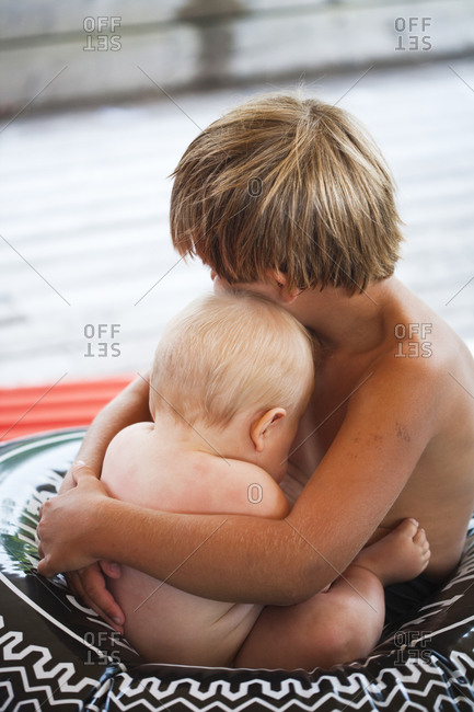Boy hugging his baby brother