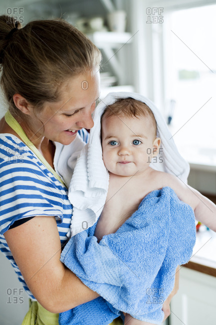 Young woman drying baby off with a towel