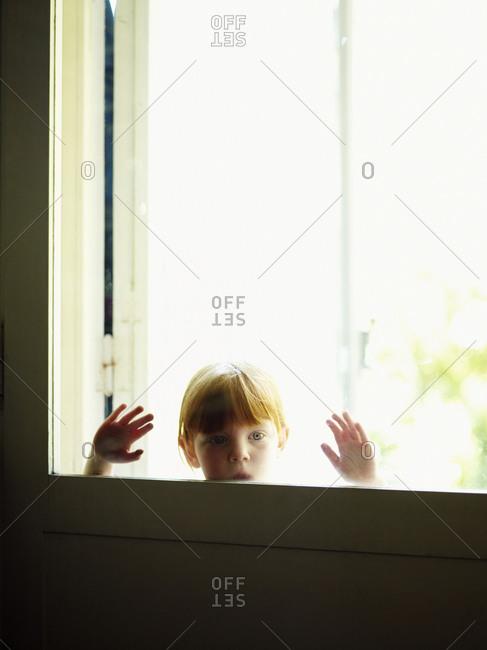 Redhead girl looking through window