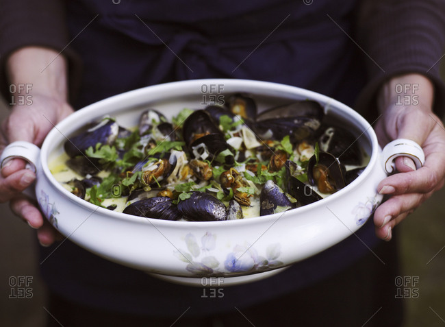 Woman serving a bowl of mussels