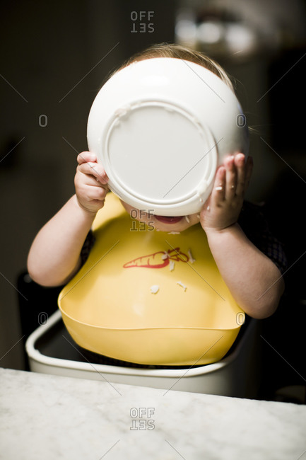 Baby boy eating from bowl