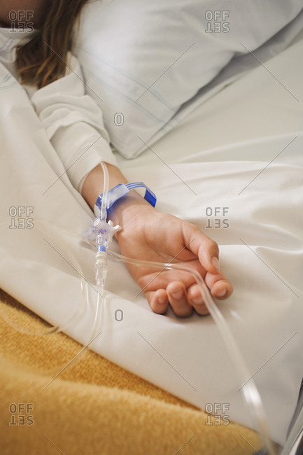 Girl lying on hospital bed with IV drip on arm